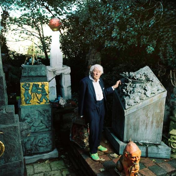 Aat veldhoen in  his garden with his art work